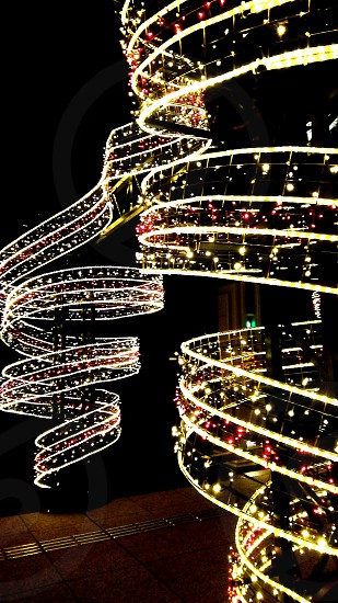 photo of spiral yellow string lights with red baubles photo