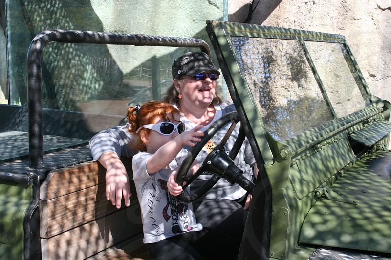 grandmother; lady; grand daughter; toddler; young girl; jeep; safari; driving; pretend; fun; silly; zoo photo