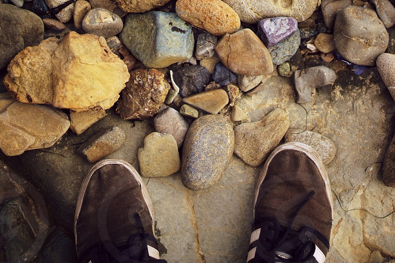 person black shoes near brown stone during daytime photo