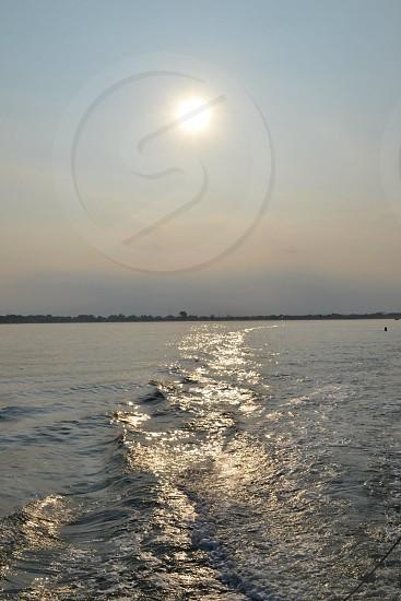 sun peering over blue ocean photo