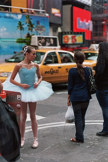 A mom had her daughter dress up and do ballet in Times Square but the daughter was very embarrassed. photo