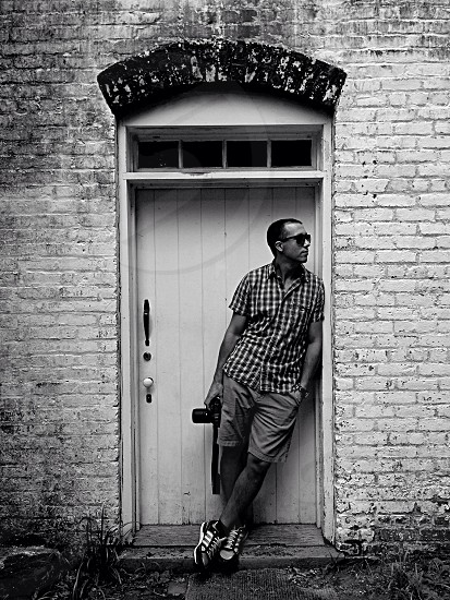 man in tattersall short sleeve collared shirt and shorts leaning on wall by doorway photo
