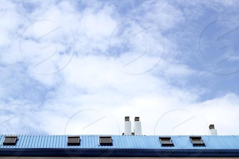 blue steel painted roof skylight windown chimney cloud sky  photo