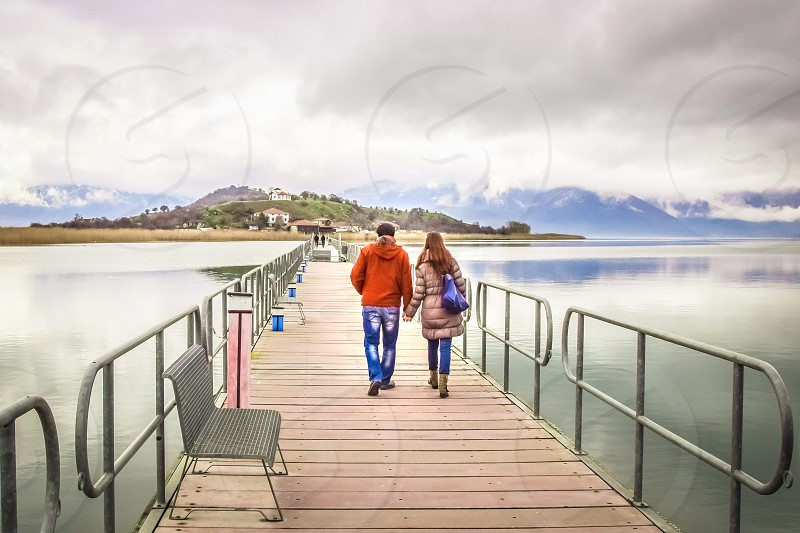 Young Couple In Love Walking Across A Bridge Holding Hands photo