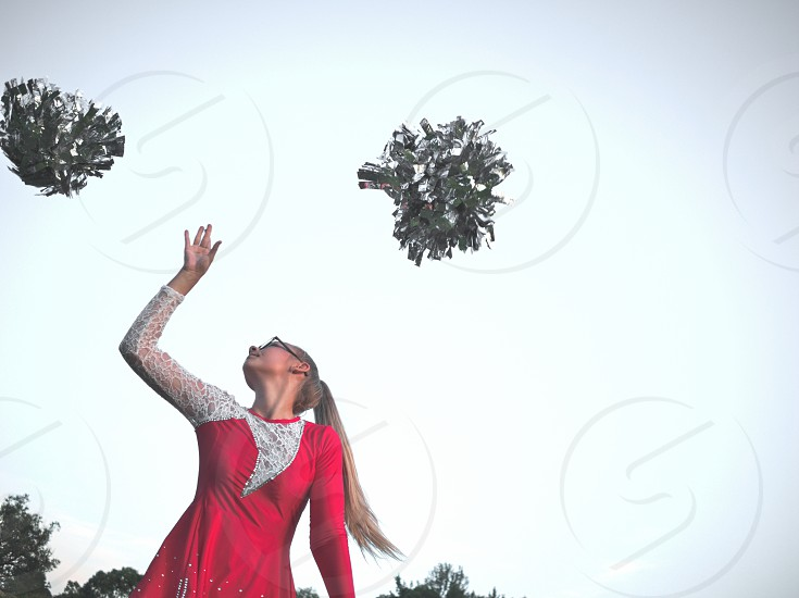Bespectacled Blonde Teen Majorette Girl with Pom-poms Outdoors in Red Dress photo
