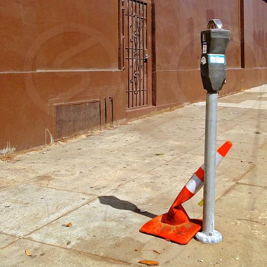 orange and white plastic road cone near parking meter photo