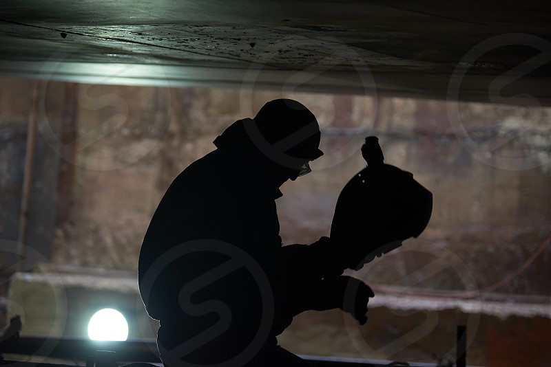 Silhouette of a welder having a break at a shipyard underneath a large vessel with fire sparks flying around everywhere photo