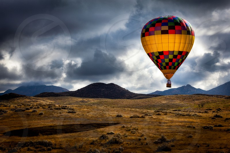 Lone hot air balloon low over an open field looking for a good spot to land on a cloudy day. photo