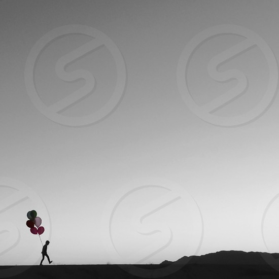 person walking near mountain holding multicolored balloons photo