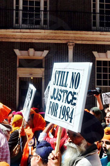 man wearing gray top holding white Still No Justice For 1984-printed sign photo