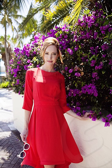 red hair woman in a red dress standing by a purple blossoming hedge photo