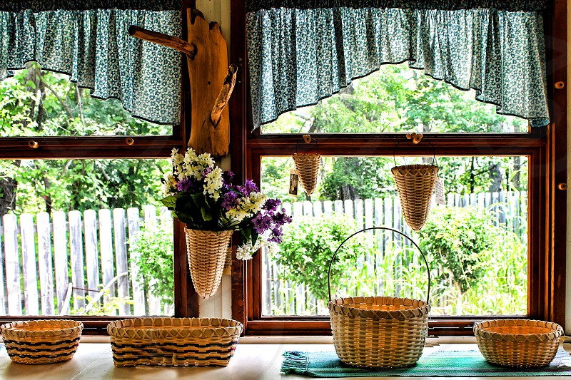 Straw baskets sit on the counter of a country kitchen near a window photo