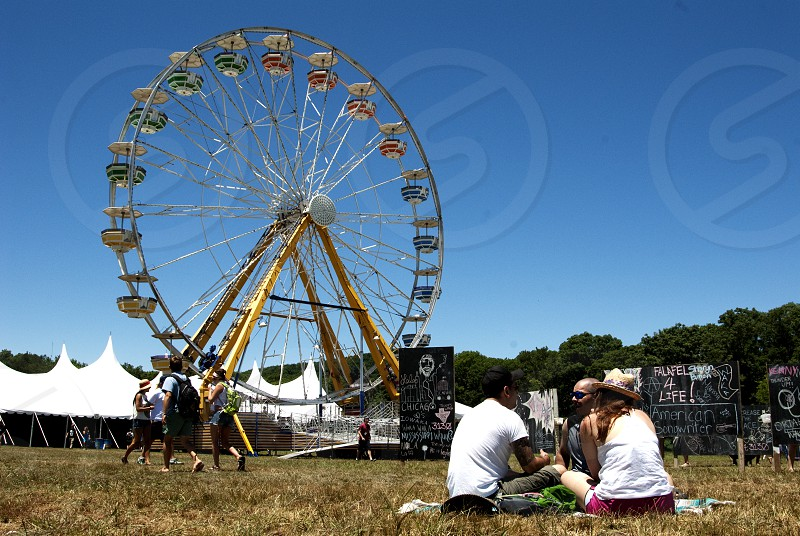 Group picnicking in front of Ferris Wheel and tent photo
