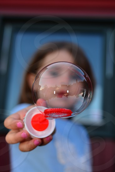 girl holding white and red bubble wand with bubbles photo