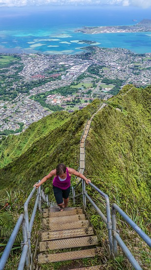 woman in purple tank top climbing on brown and gray metal staircase in green mountain with an aerial photo background of urban area near body of water during daytime photo