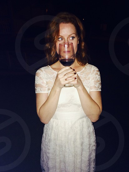 woman holding a wine glass over her face photo