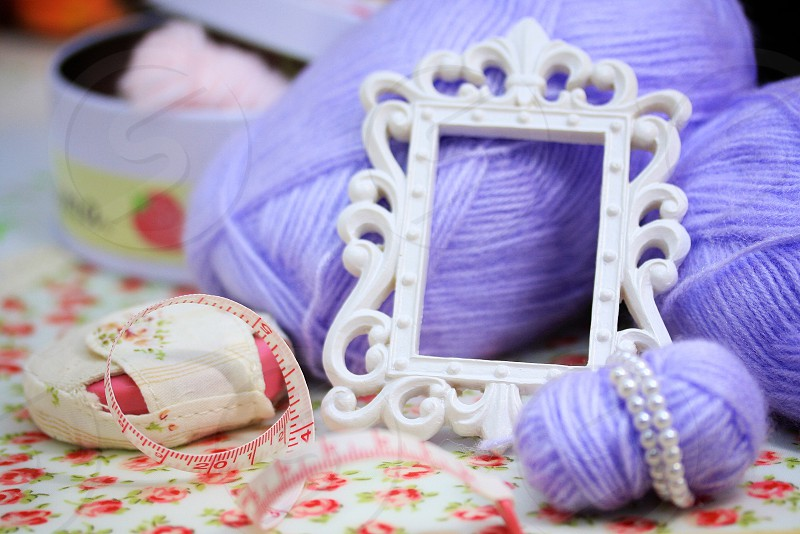 white floral design picture frame on top of purple yarn rolls photo