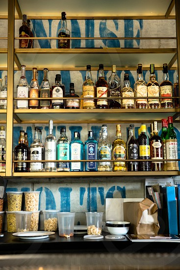clear glass bottles on brown wooden shelf above clear plastic container photo