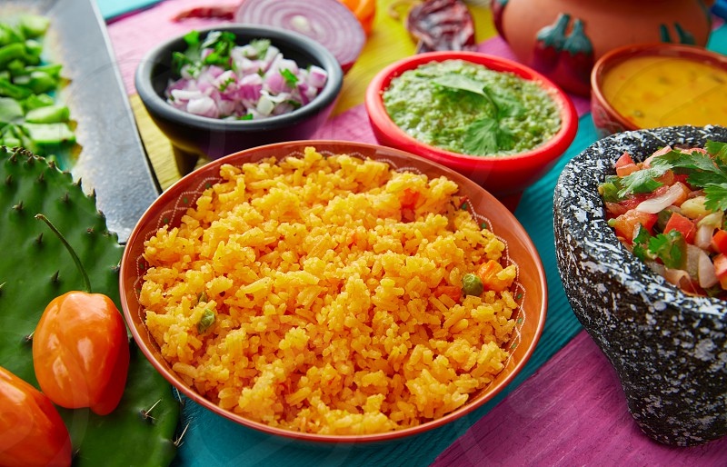 Mexican yellow rice with chilis and sauces in colorful background photo