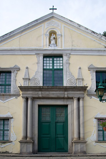 White Religious Cross Building with Green Doors photo