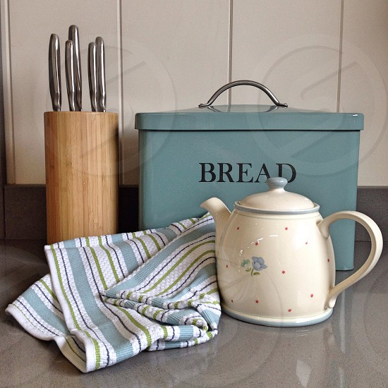 white and blue polka dot teapot beside blue green and white stripe textile photo