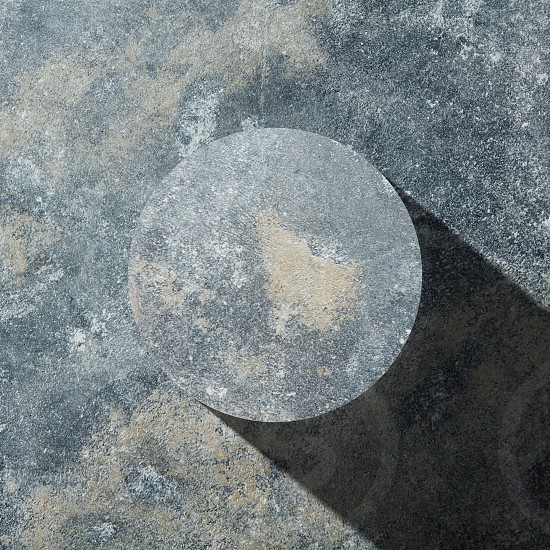 granite circle with shadow isolated on dark stone background flat lay photo