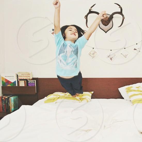 Kid wearing vintage tee jumping on bed photo