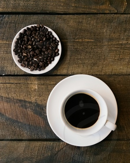 Black coffee and coffee beans on a plate shot from above photo