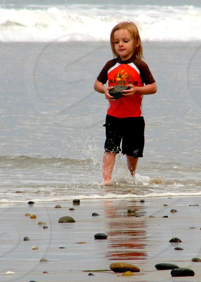 kid carrying stone from beach photo