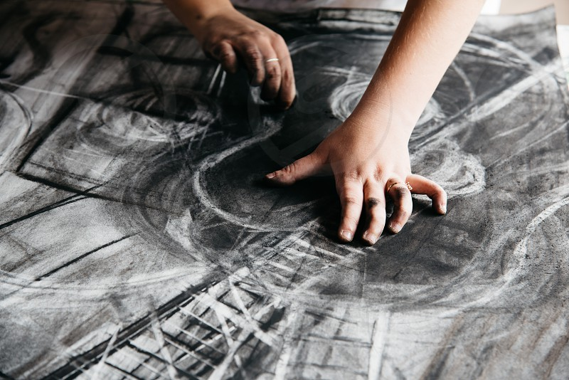 Young female artist painting with charcoal on paper photo