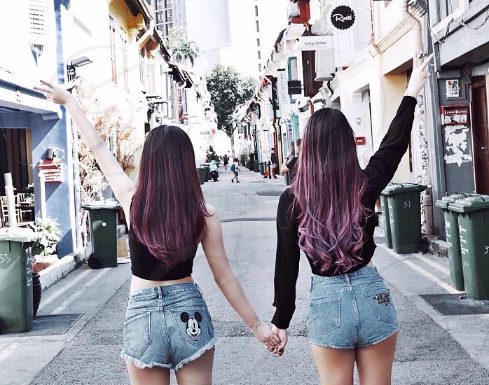 2 purple haired woman making a peace hand sign in the middle of the street during daytime photo