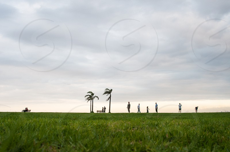 outdoor shot over green grass in the distance diverse groups of little tiny people connected and inspired by nature versus the grandness of nature photo
