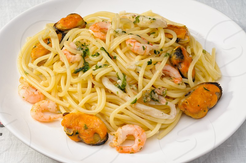 Close up of italian spaghetti with mussels shrimps and squid in a white plate photo