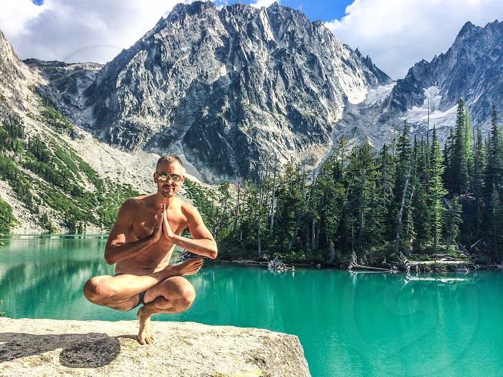Zen moment after a long hike. Yoga pose: half lotus toe stand.  photo