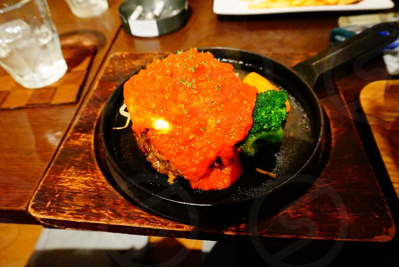 orange meat and broccoli on black frying pan photo
