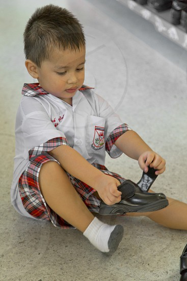 Back to school kid sitting on the floor wearing shoes photo