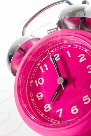 pink alarm clock set to 8:00 photo
