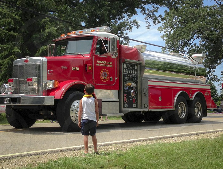 A little boy staring up in awe at large firetruck in the Fourth of July parade. photo
