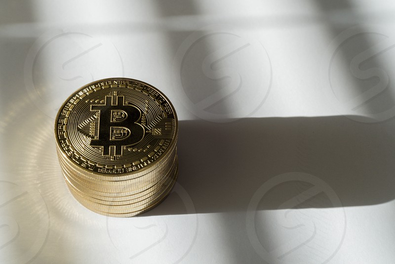 Bitcoin digital currency gold token coins stacked with shadows and light. photo