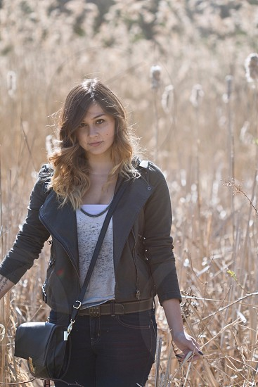 woman in black leather jacket on brown grass field photo
