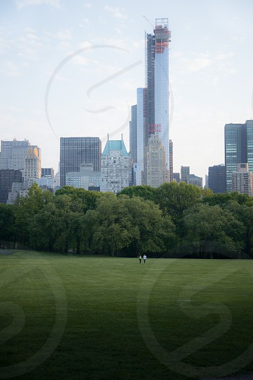 view of green grass field and city tower buildings photo