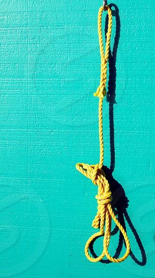 Yellow nautical rope hangs on an aqua background. photo