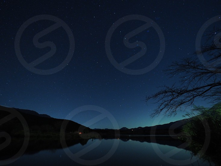 body of water between mountains during nighttime photo