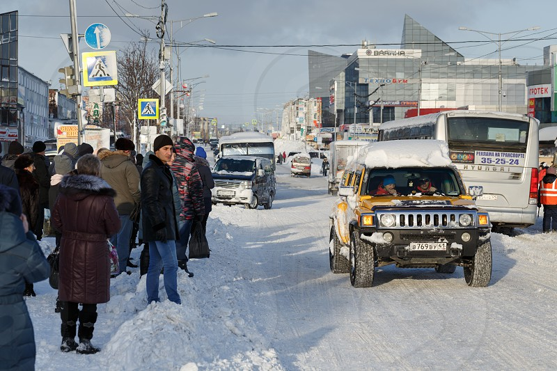 PETROPAVLOVSK CITY KAMCHATKA RUSSIA - DECEMBER 27 2017: Winter city landscape after snowstorm - people in anticipation of public transport are standing on carriageway of city road in bus stop area photo