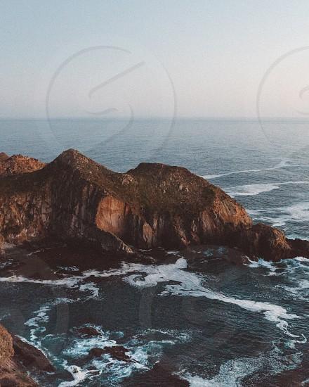 Ocean cliff Pacific beach water surf waves wave submerge surf break  photo