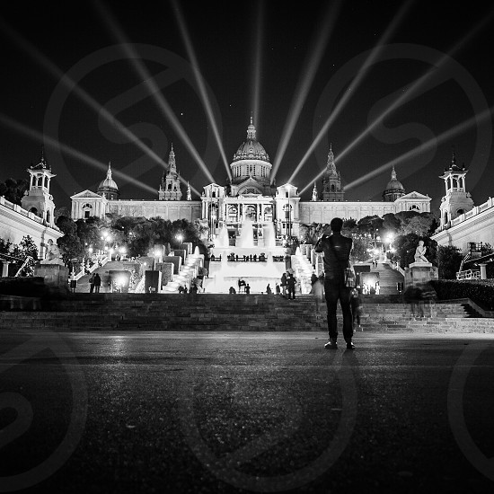 person taking picture of palace  in gray scale photography photo