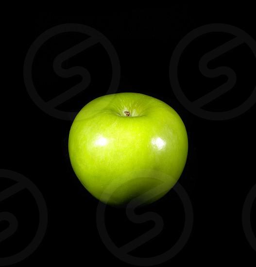fresh vivid green apple over black background photo