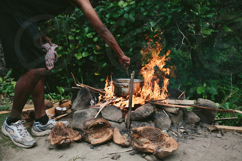 Fire cooking BBQ stone fire bomb fire entertainment danger eating light torch day fiji pacific smoke lunch food home made authentic basic photo