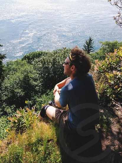 man sitting on cliff photo