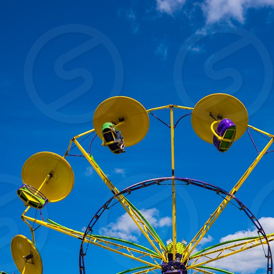A yellow fair ride on a blue sky day. photo